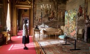 Uma mulher olha para o Cão com os cascos dos cavalos no Palácio de Blenheim.