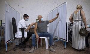 An Israeli man takes a selfie while receiving a Pfizer-BioNTech Covid-19 vaccine in Ramat Gan.