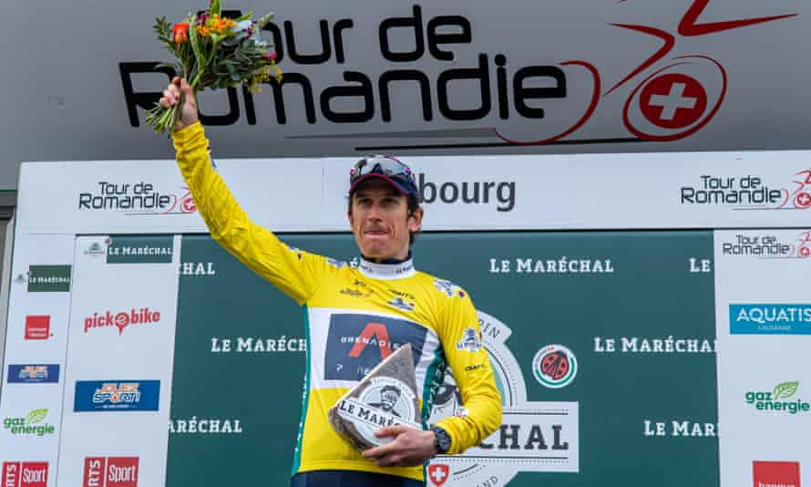Geraint Thomas hold his flowers aloft after winning the title.