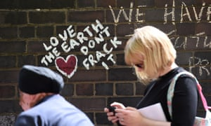 People walk past anti-fracking messages written on a wall during a demonstration outside Lancashire county hall in Preston.