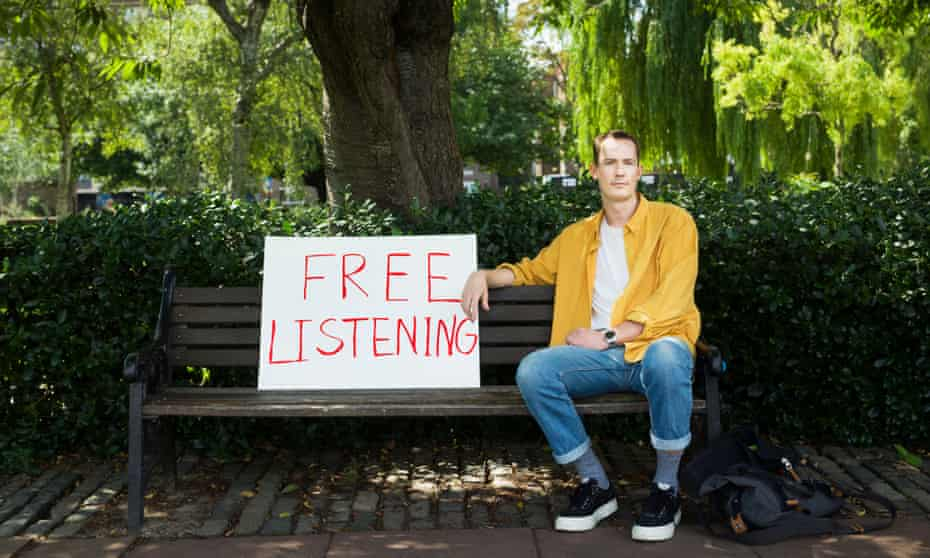 Jamie Waters sitting on a park bench with a big sign next to him saying 'free listening'