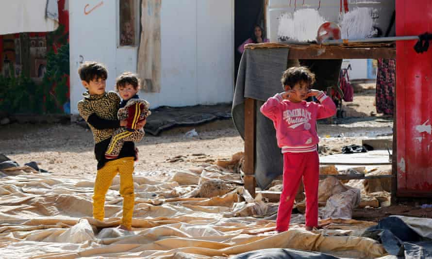 Syrian refugee children in front of their family caravan in Al Zaatari refugee camp in Jordan near the border with Syria