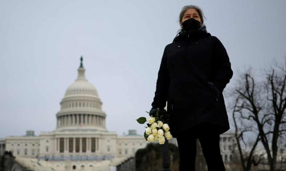 Azhenedt Sanabria holds flowers as she pays her respects to the late Capitol police officer Brian Sicknick, who died on Thursday from injuries he sustained while defending the US Capitol from a pro-Trump mob.