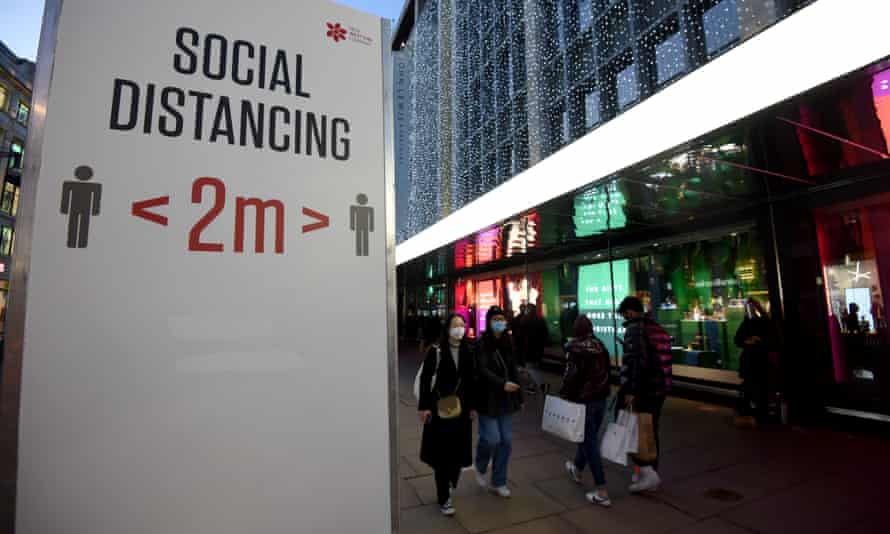 Shoppers walk past social distancing signs on Oxford Street.