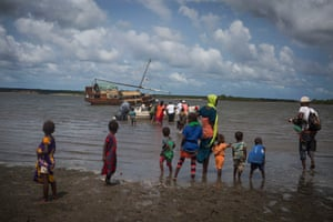 Women and children watch as the medical team head back to the boat after a clinic