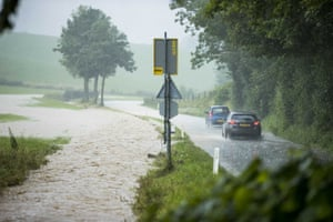 Cars drive near flooded fields in Ubachsberg, the Netherlands