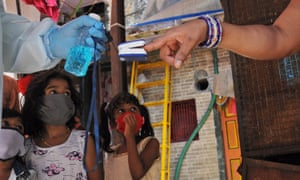 A healthcare worker screens a resident of Dharavi for coronavirus in June.