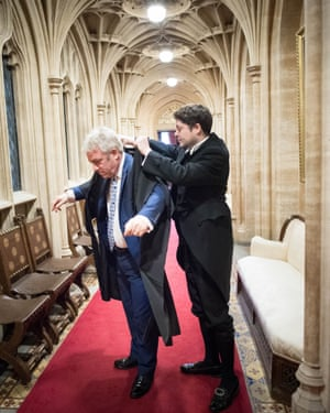 A male aide puts on Bercow's gown in a corridor in the House of Commons