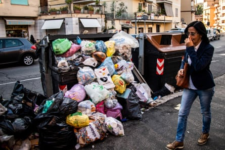 A woman walks past overflowing rubbish bins holding her nose