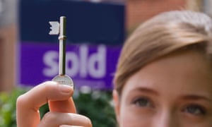 A young woman holding a door key in front of a sold sign