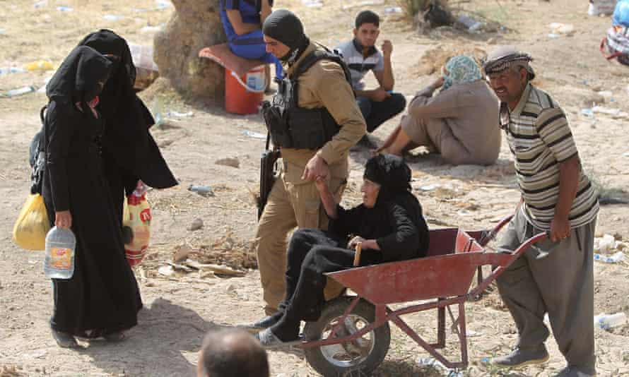 An elderly Iraqi woman who fled from the city of Ramadi, which is besieged by Isis militants, is pushed in a wheelbarrow as she holds the hand of an armed man as people wait to cross Bzeibez bridge.