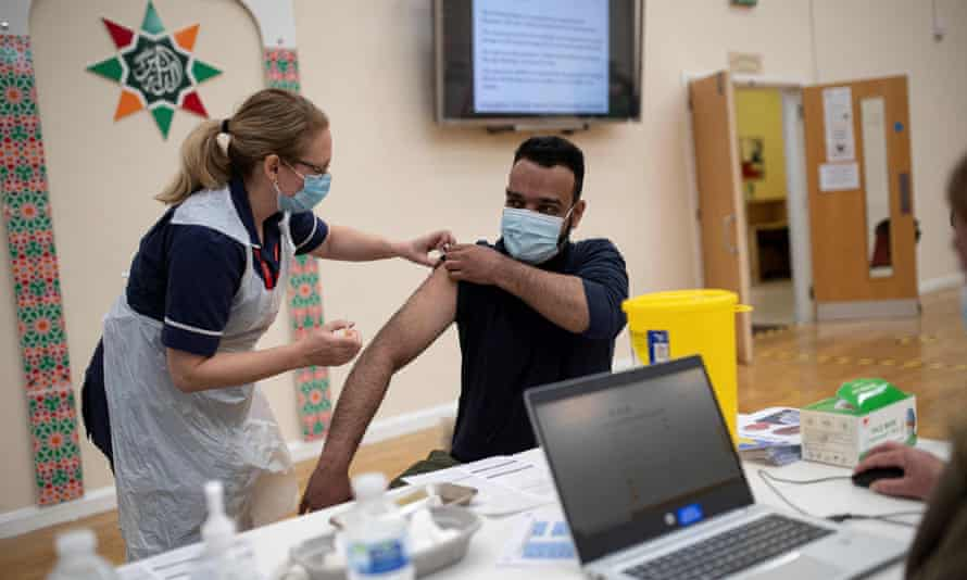A health worker administers a dose of AstraZeneca at a vaccination centre set up at a mosque in Nottingham