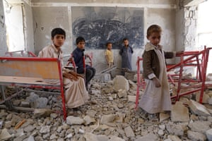Young students in Sa'ada stand amid the ruins of a classroom destroyed in the Yemen conflict