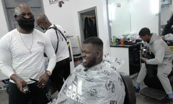 Khallid Muhammad sitting in a barber's chair