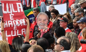 A supporter of Brazilian former president Luiz Inácio Lula da Silva holds a mask depicting him, as they gather outside the federal police building in Curitiba on Tuesday.
