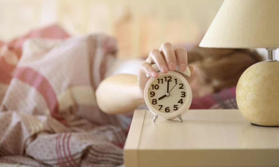 Woman turns off the alarm clock
