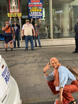 Shaymaa Ismaa'eel, a 24-year-old Muslim woman passes by a group of angry protesters at an Islamic conference in Washington DC.. In response, she crouched in front of them and flashed a peace sign. The photo, posted on Instagram, prompted an outpouring of support.