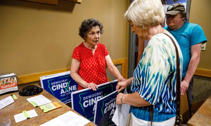 Jan Lunde hands out yard signs to Carol Preston of during a town hall meeting for Iowa Democratic congressional candidate Cindy Axne.