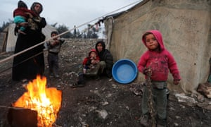 Displaced Syrian women and children, who fled north from Idlib, gather around a fire in Afrin.