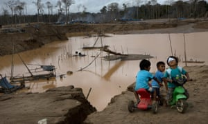 Children play next to a large crevice created by illegal gold mining in La Pampa, in Peru's Madre de Dios region