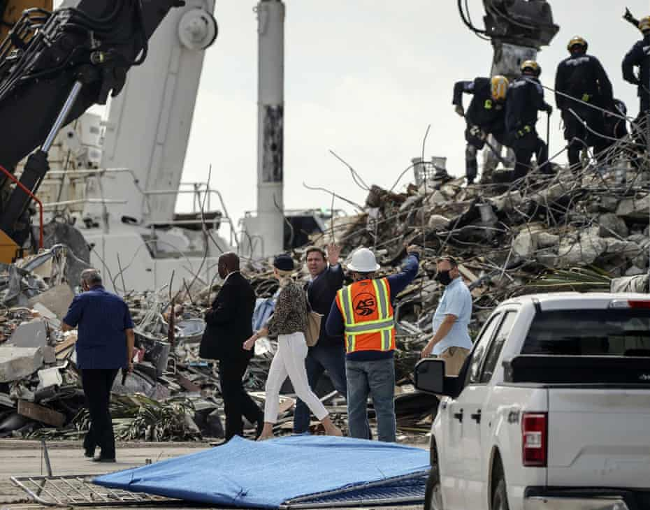 Florida's governor, Ron DeSantis, center, tours the site of the Champlain Tower South complex on Monday.