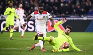 Moussa Dembele in Lyon scoops, but the ball is blocked by Barcelona's Gerard Pique.