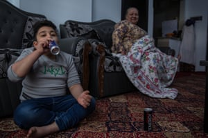 Emran, eight, drinks an energy drink at his house in Kabul.