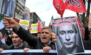 Turkish protesters in Istanbul shout anti-Russia slogans as they hold a poster of Vladimir Putin that reads 'Assassin Putin!'