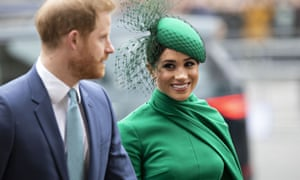 Meghan, in a green dress with a cape and a cocktail hat with netting, smiles as he walks with Prince Harry.