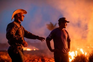 A labourer and his friend watch a fire that spread to the farm he works on next to a highway in Nova Santa Helena.