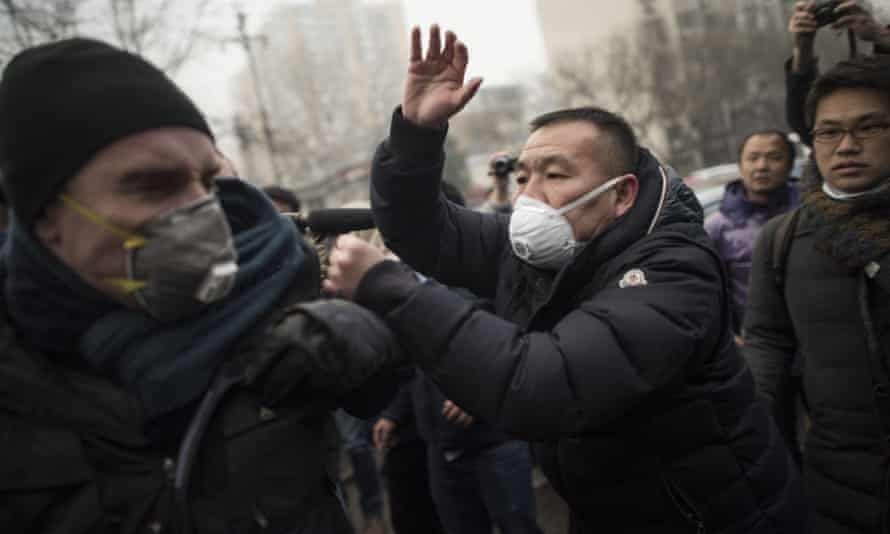 Chinese police push away journalists during the trial of Pu Zhiqiang in Beijing in December 2015.