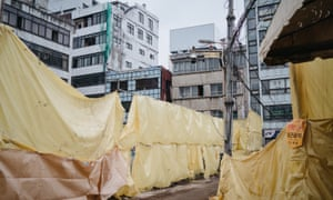 Yellow tarp and scaffoldings cover the area where demolition of old buildings is in progress, Euljiro, Seoul.