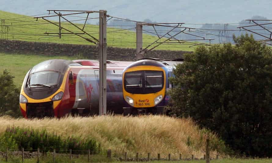 a Virgin train passing a First Group train