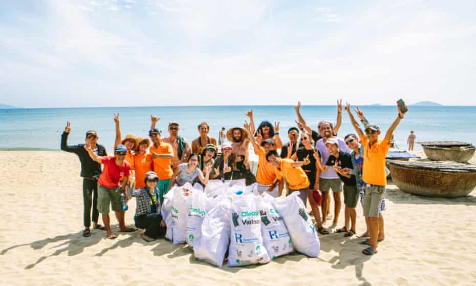 Travellers on Intrepid Travel's Peloton Against Plastic cycling tour take part in a beach clean up in Hoi An, Vietnam.