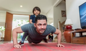 Father doing pushups with son on back