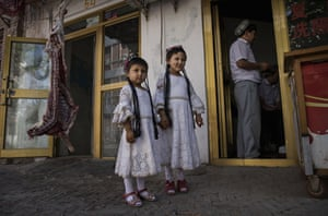 Girls in traditional clothing stand outside a butcher shop