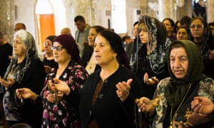 Women attend Maundy Thursday mass at Mar Hanna (St John's) church in Hamdaniya.