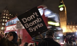 A protester holds a placard reading 'Don't attack Syria' outside parliament on the eve of the Commons vote.