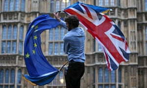 A man waves both a Union flag and a European flag together on College Green outside parliament.