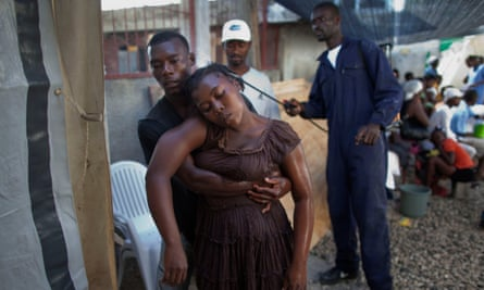 A worker sprays disinfectant over a woman with symptoms of cholera as she is held by a relative in Haiti in 2010.