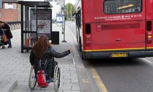 A wheelchair user hailing a bus.