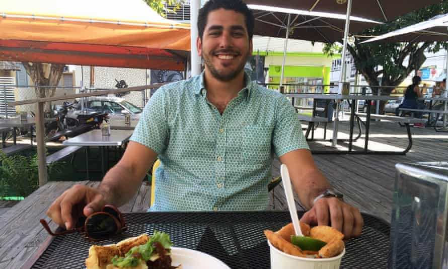 Gustavo Antonetti sitting outside at Tresbé restaurant with food in front of him.