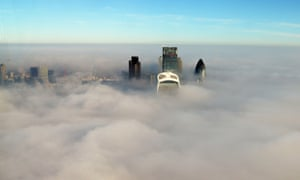 London's skyscrapers emerge above the fog on Monday.
