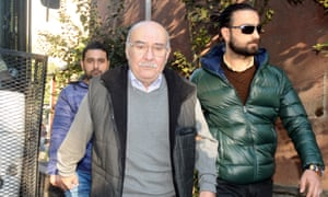 Aydin Engin is escorted by plainclothes police officers from his home on 31 October.