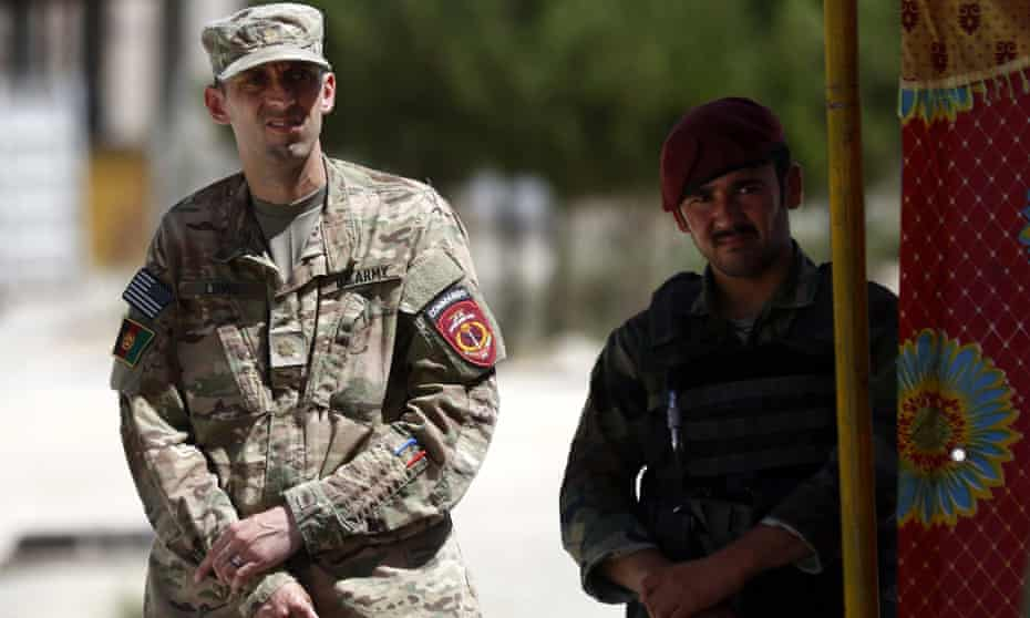 A US soldier stands beside an Afghan soldier as they inspect the scene of the suicide bomb in Kabul, Afghanistan.