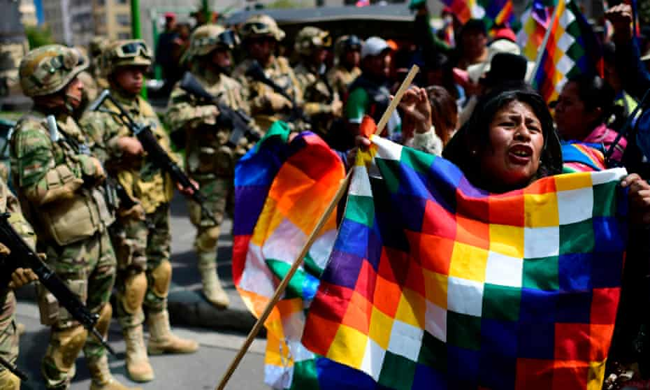 A Bolivian indigenous woman, supporter of Bolivian ex-president Evo Morales, holds a Wiphala flag –representing native peoples – during a protest against the interim government in La Paz on 15 November.