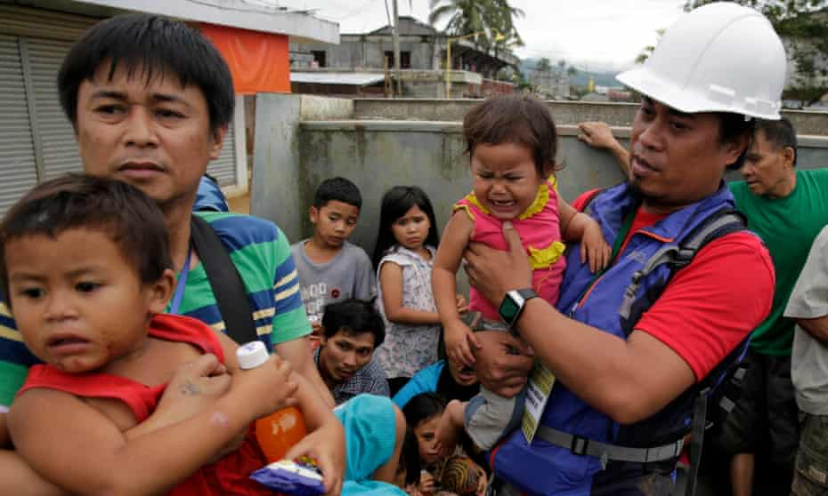 Children are carried to safety during a rescue operation in Marawi