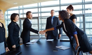 Business people shaking hands across tableLarge group of corporate business people