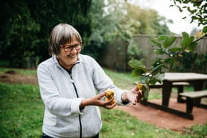 "A volunteer, who describes the community of guides at Westonbirt as ""like a family"" shows the fruit of a quince tree"