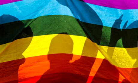 Silhouettes of people against a rainbow flag